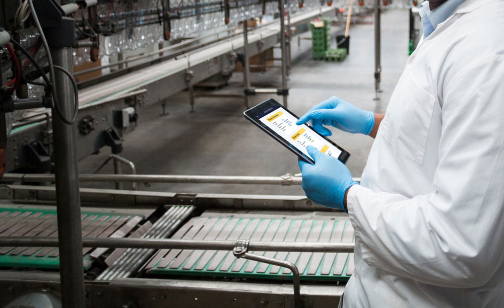 Person using tablet with Hx Manager controlling Hx Nitro thermal inkjet printer in the production line